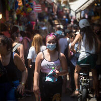 Israelis, some wearing face masks, as they shop in the Carmel Market in Tel Aviv, on July 26, 2021. (Miriam Alster/Flash90)