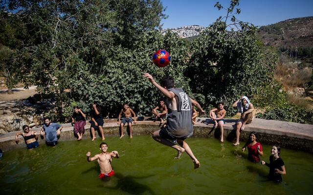 People enjoy a hot summer day at the Ein Lavan Spring in the Jerusalem Mountains, July 28, 2021. (Yonatan Sindel/Flash90)