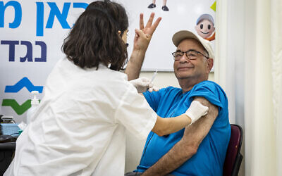 Israelis above 60 years old receive their third dose of the COVID-19 vaccine at a Clalit health care maintenance organization, on August 01, 2021, in Jerusalem. (Olivier Fitoussi/Flash90)