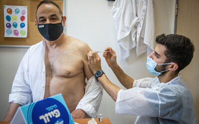 An Israeli receives a coronavirus booster shot at a Maccabi Healthcare Services vaccination center, on August 1, 2021. (Yonatan Sindel/Flash90)