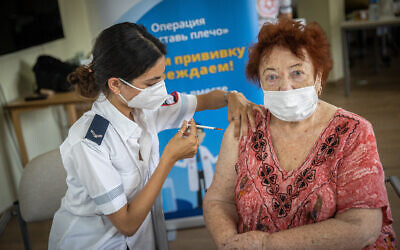 A resident from Amigor retirement residence receives her third COVID-19 vaccine dose from Magen David Adom worker at Amigor retirement residence in Jerusalem on August 4, 2021. (Yonatan Sindel/Flash90)