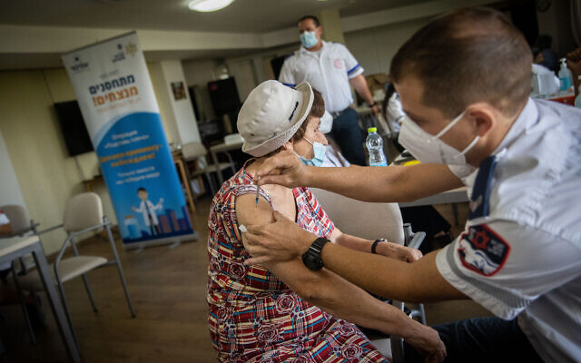 An elderly Israeli receives a third COVID-19 vaccine dose at a retirement residence in Jerusalem on August 4, 2021. (Yonatan Sindel/Flash90)
