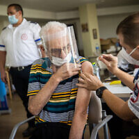 A resident from the Amigor elder care facility receives a third dose of the coronavirus vaccine on August 4, 2021. (Yonatan Sindel/Flash90)