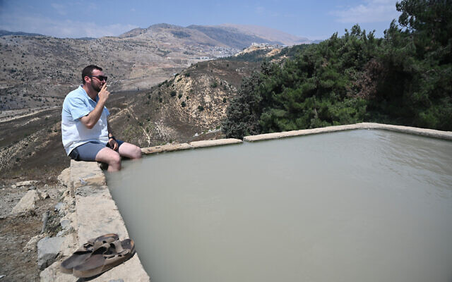 A man sits in a water spring in the Golan Heights, northern Israel, during the summer vacation, on August 6, 2021. (Michael Giladi/Flash90)