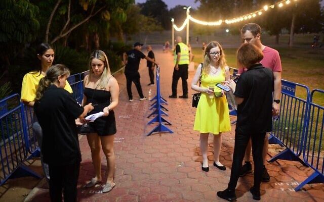 Israelis present their COVID-19 vaccination certificates at the entrance to a concert venue n Tel Aviv on August 7, 2021 in Tel Aviv. (Tomer Neuberg/ Flash90)