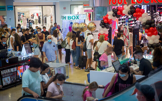 Israelis wearing face masks walk inside Dizengoff Center in Tel Aviv on August 9, 2021. (Miriam Alster/Flash90)