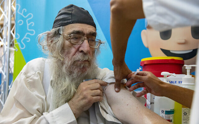 Israelis over 60 receive their third-dose booster of the COVID-19 vaccine at a Clalit HMO clinic in Jerusalem, on August 8, 2021. (Olivier Fitoussi/Flash90)