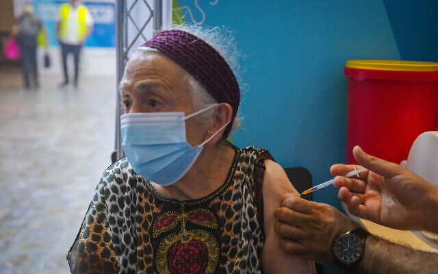An Israeli woman over 60 receives a third coronavirus vaccine shot at a Clalit health clinic in Jerusalem on August 8, 2021. (Olivier Fitoussi/Flash90)