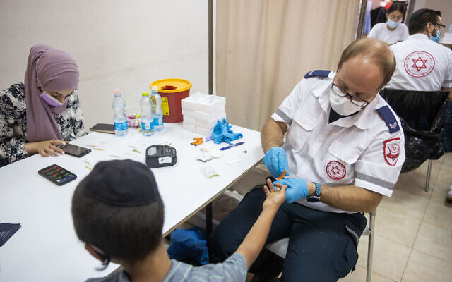 A Magen David Adom worker takes blood for a serological test for COVID-19 from an child in the ultra-Orthodox town of Kiryat Ye'arim (Telz-Stone), outside Jerusalem, on August 9, 2021. (Yonatan Sindel/Flash90)