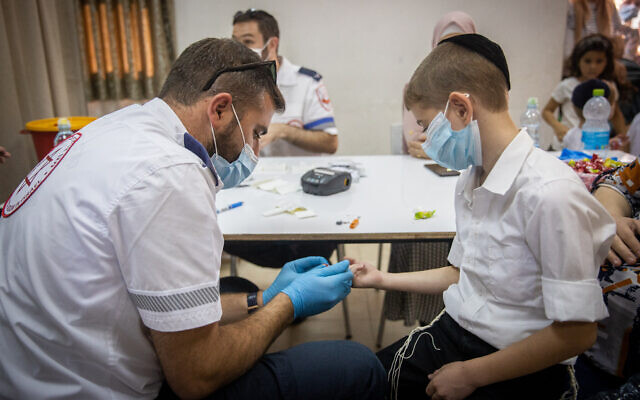 Magen David Adom worker carries out a serological test for COVID-19 in the ultra-Orthodox town of Kiryat Ye'arim, August 9, 2021 (Yonatan Sindel/Flash90)