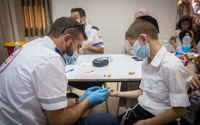 A Magen David Adom paramedic takes blood for serological tests on ultra-Orthodox school kids in Kiryat Yearim on August 9, 2021. (Yonatan Sindel/Flash90)