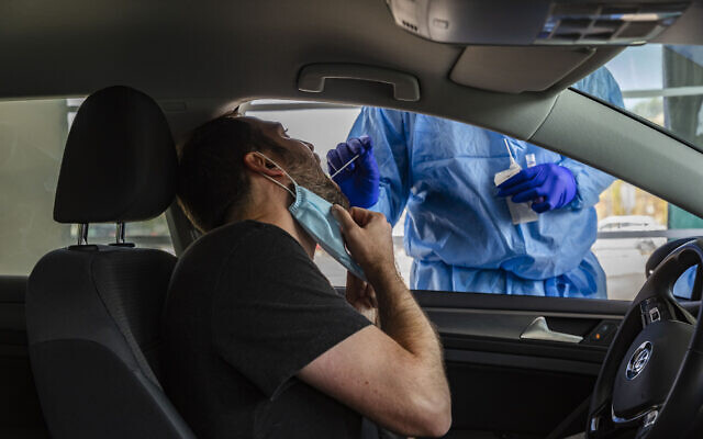 A healthcare worker takes a swab sample from a man at a drive-thru coronavirus testing facility in Jerusalem, on August 10, 2021. (Olivier Fitoussi/Flash90)