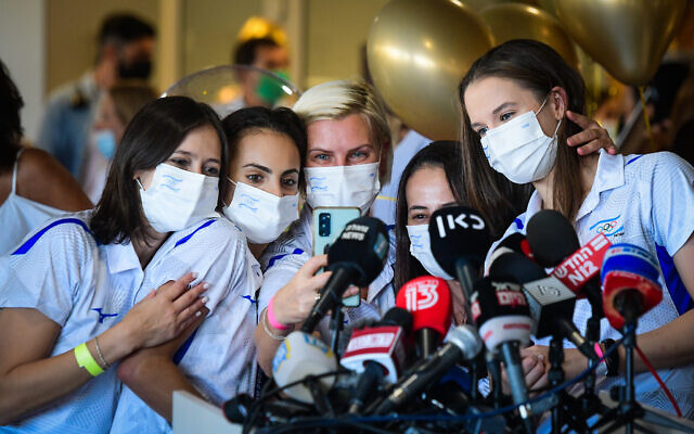 Olympic Gold medalist Linoy Ashram (2L) is greeted by press, family and friends as she arrives at Ben Gurion Airport after winning the Gold medal in the rhythmic gymnast at the Olympic Games in Japan, August 11, 2021. (Avshalom Sassoni/Flash90)