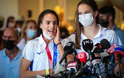 Olympic Gold medalist Linoy Ashram (L) and teammate Nicol Zelikman at Ben Gurion Airport, August 11, 2021. (Avshalom Sassoni/Flash90)