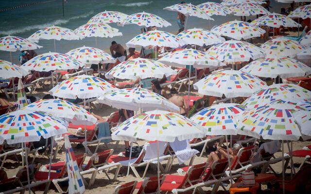 Israelis enjoy the beach in Tel Aviv on a hot summer day. August 11, 2021. (Miriam Alster/Flash90)