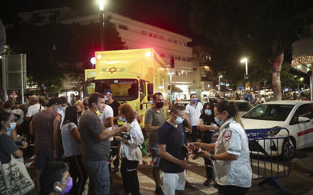 Israelis line up to receive coronavirus vaccines at a vaccination station operated by the Magen David Adom ambulance service, in Tel Aviv, on August 14, 2021. (Miriam Alster/Flash90)