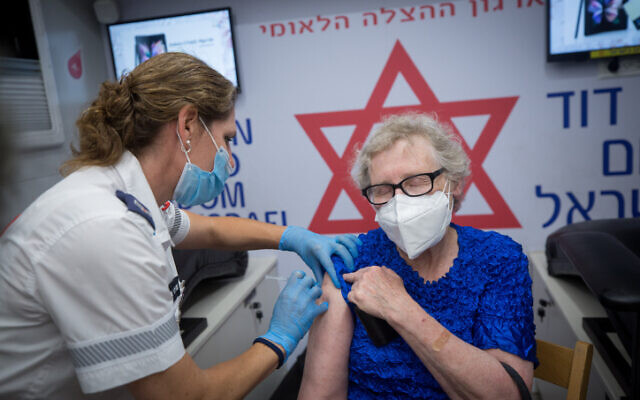 A woman receives a COVID-19 vaccine shot at a mobile Magen David Adom center on Dizengoff Square in Tel Aviv, on August 14, 2021. (Miriam Alster/Flash90)