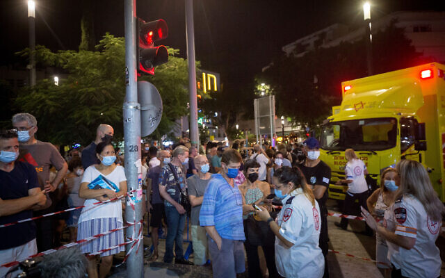 Israelis stand in line to receive the COVID-19 vaccine at a mobile Magen David Adom center on Dizengoff Square in Tel Aviv, on August 14, 2021 (Miriam Alster/Flash90)