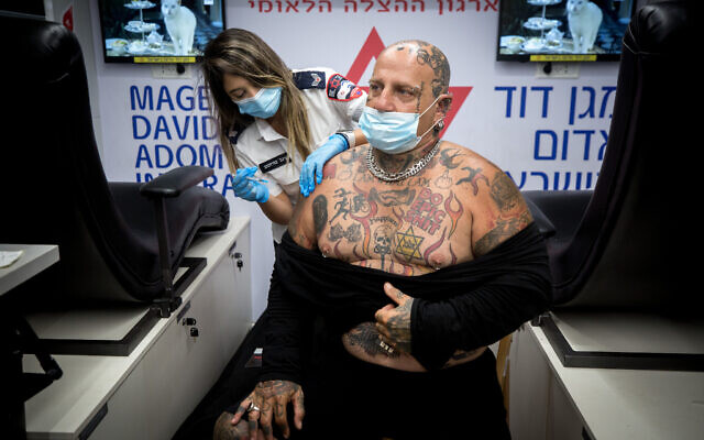 An Israeli man receives a COVID-19 vaccine during a mass vaccination drive at Dizengoff Square in Tel Aviv, on the night of August 14, 2021. (Miriam Alster/Flash90)