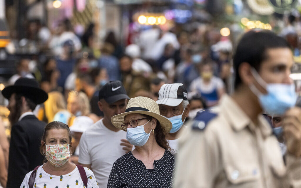 People, some with face masks, shop at the Mahane Yehuda market in Jerusalem on August 15, 2021. (Olivier Fitoussi/Flash90)
