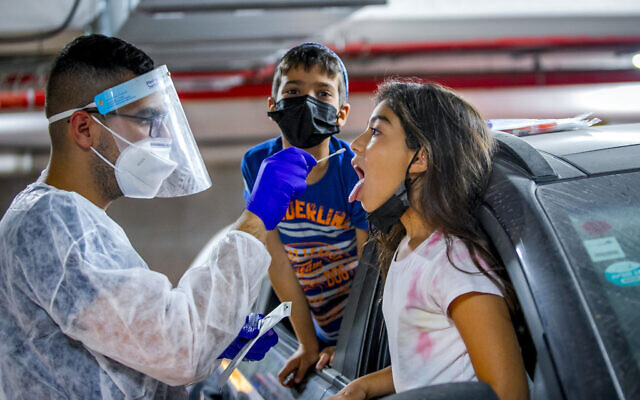 Healthcare workers test a child for coronavirus at a Maccabi drive through complex in Modiin on August 15, 2021. (Yossi Aloni/Flash90)