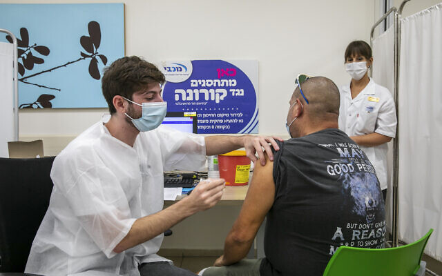 People receive their COVID-19 vaccine at a vaccination center in Modiin on August 15, 2021. (Yossi Aloni/Flash90)
