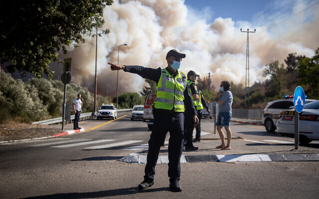 A policeman directs traffic as smoke from a wildfire billows outside of Jerusalem on August 15, 2021. (Yonatan Sindel/Flash90)