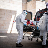 Magen David Adom workers wearing protective clothing evacuate a patient suspected of carrying the virus that causes COVID, at Hadassah Hospital Ein Karem in Jerusalem on August 15, 2021. (Yonatan Sindel/Flash90)