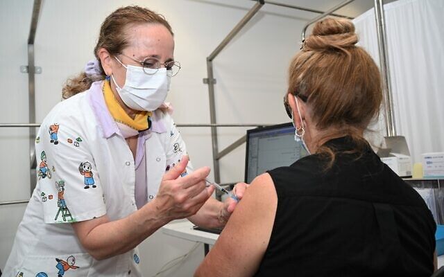 An Israeli woman who is at least 50 years of age receives a coronavirus vaccine booster shot at a Clalit Healthcare Services facility in the Golan Heights town of Katzrin on August 16, 2021. (Michael Giladi/Flash90)