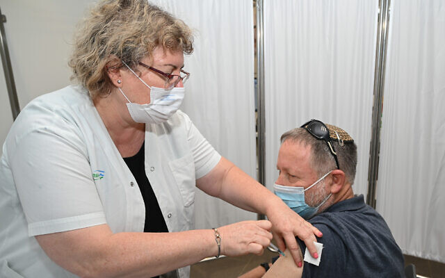 A man receives a third dose of the coronavirus at a health center in Katzrin, on the Golan Heights, August 16, 2021. (Michael Giladi/Flash90)