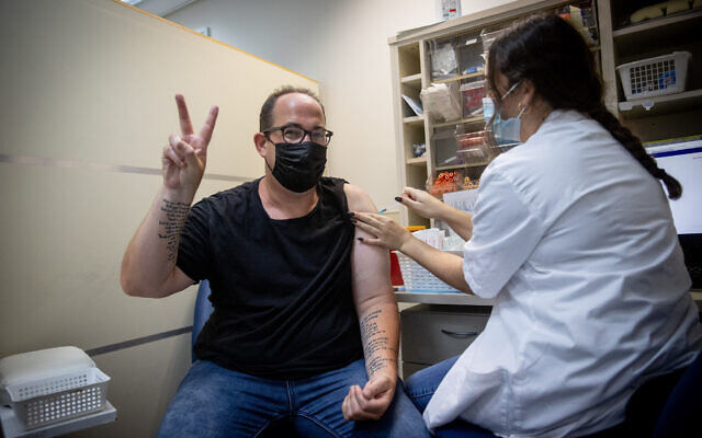 An Israeli man receives a third dose of the COVID-19 vaccine, at a Maccabi healthcare services vaccination center, on August 22, 2021. (Yonatan Sindel/Flash90)