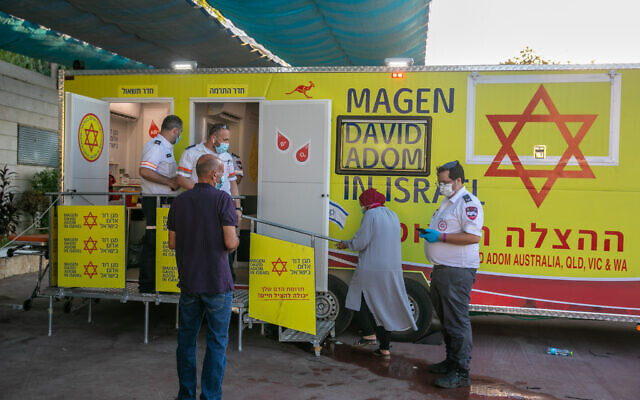 Israelis stand in line to receive the COVID-19 vaccine at a Magen David Adom mobile vaccine unit in the town of Kafr Qasim on August 23, 2021. (Yossi Aloni/Flash90)