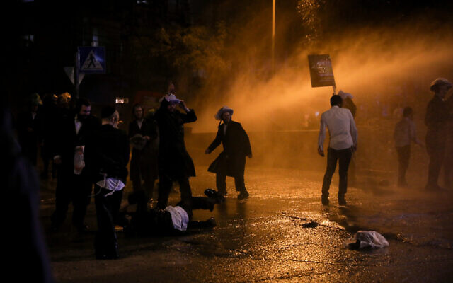 Ultra-Orthodox Jews clash with police to protest work on a new light, on Bar Ilan Street in Jerusalem, on August 24, 2021. (Noam Revkin Fenton/Flash90)