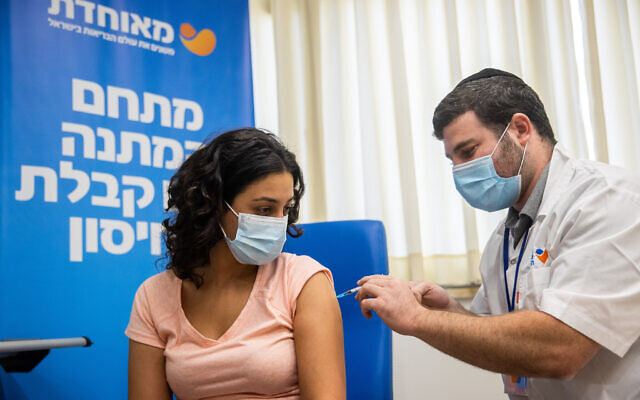 An Israeli teacher receives a dose of the COVID-19 vaccine, at a vaccination center in Jerusalem, on August 24, 2021. (Yonatan Sindel/Flash90)