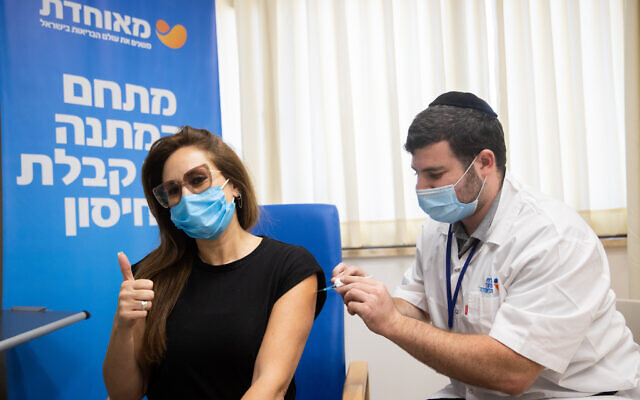 A woman receives a third dose of the COVID-19 vaccine, at a Meuhedet  vaccination center in Jerusalem, on August 24, 2021. (Yonatan Sindel/Flash90)