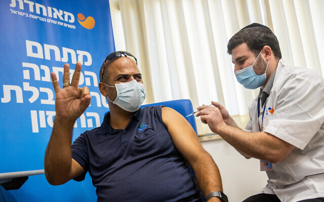 A man in his 30s receives a third COVID-19 vaccine dose, at a vaccination center in Jerusalem, on August 24, 2021. (Yonatan Sindel/Flash90)
