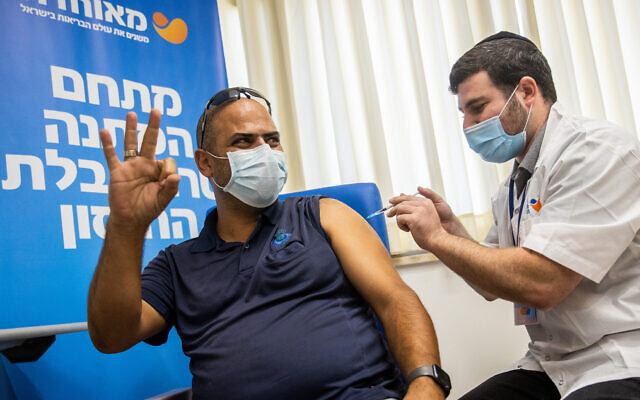 A man receives a coronavirus vaccine booster at a Meuhedet vaccination center in Jerusalem, on August 24, 2021. (Yonatan Sindel/Flash90)