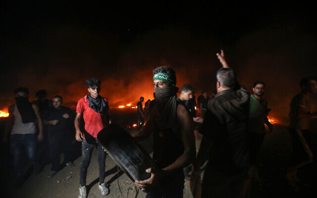 Palestinian burn tires during rioting along the border between the Gaza Strip and Israel, east of Gaza City, on August 28, 2021. (Atia Mohammed/Flash90)