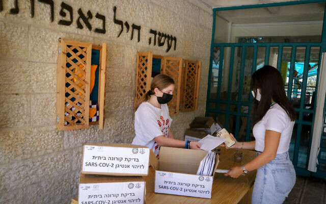 Parents receive COVID-19 home testing kits ahead of the opening of the new school year in the settlement of Efrat, in Gush Etzion, August 29, 2021. (Gershon Elinson/Flash90)