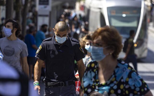 Israelis, some wearing face masks, walk on Jaffa Street in Jerusalem, August 29, 2021. (Olivier Fitoussi/Flash90)