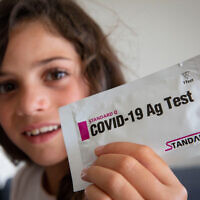 A child poses with her COVID-19 home kit test that she received from her school, ahead of the opening of the new school year, in Jerusalem, August 30, 2021. (Olivier Fitoussi/Flash90)