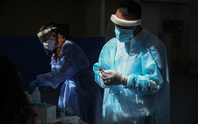 Health workers handle samples at a temporary COVID-19 testing facility in the northern city of  Safed, on August 31, 2021. (David Cohen/Flash90)