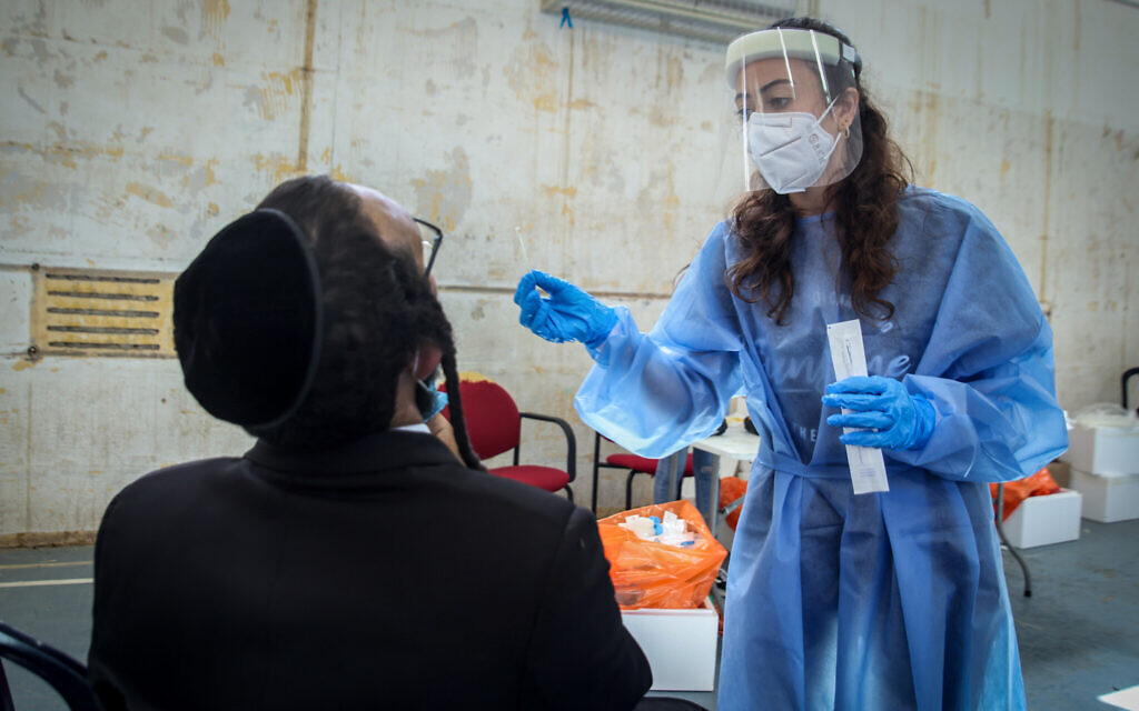 A health worker takes a swab sample on from a man at a temporary COVID-19 testing facility in the northern city of  Safed, on August 31, 2021. (David Cohen/Flash90)