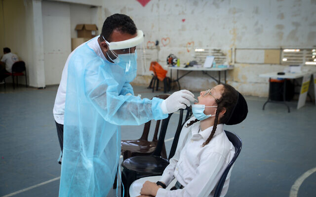 Health personnel take test samples on Israelis wanting to travel abroad, at a COVID-19 testing station in Safed, on August 31, 2021. (David Cohen/Flash90)