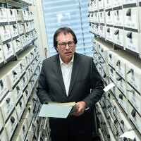 Senior Public Prosecutor Thomas Will, head of the Central Office of the State Justice Administrations for the Investigation of National Socialist Crimes, stands among the files used for the work of the Central Office at the branch office of the Federal Archives in Ludwigsburg. (Sebastian Gollnow/picture alliance via Getty Images via JTA)