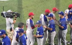Players on Israel's national baseball team shake hands with their counterparts from the Dominican Republic after losing 7-6, ending the Israeli squad's run at the 2020 Tokyo Olympics, August 3, 2021. (Amit Shisel/Israel Olympic Committee)