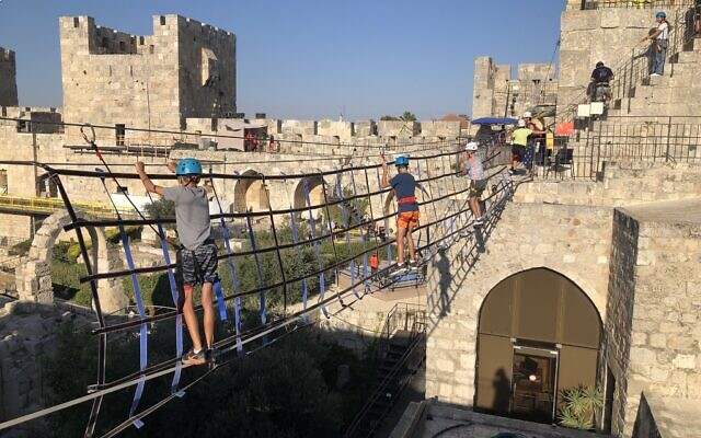 Walking across a hanging bridge in the Tower of David Museum ropes course, open in August 2021. (Jessica Steinberg/Times of Israel)