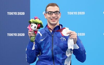 Israeli swimmer Ami Dadaon shows off the silver medal he won at the Tokyo Paralympics on August 28, 2021. (Lilach Weiss/Israel Paralympic Committee)