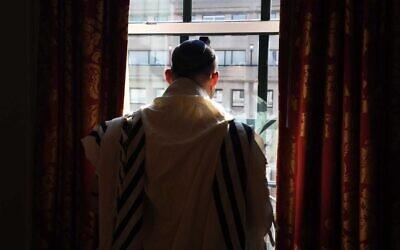 Prime Minister Naftali Bennett recites morning prayers at his hotel in Washington on August 25, 2021. (Avi Ohayon/GPO)