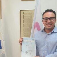 Kuwaiti-born Mark Halawa holding his new Israeli citizenship documentation, August 2021. (courtesy)